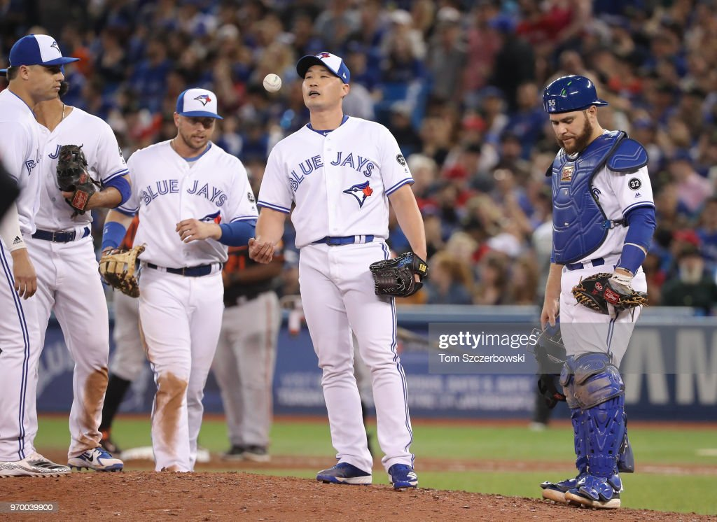 Seunghwan Oh #22 of the Toronto Blue Jays flips the ball moments before being relieved by manager John Gibbons #5 in the eighth inning during MLB game action against the Baltimore Orioles at Rogers Centre on June 8, 2018 in Toronto, Canada.
