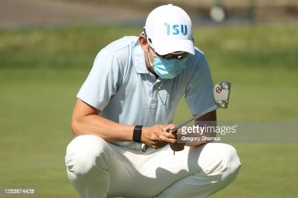 Seung-Yul Noh of South Korea wears a mask as a COVID-19 precaution as he warms up on the practice green during the first round of the Rocket Mortgage...