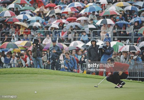 Seve Ballesteros of Spain contemplates his putt as spectators cover themselves with umbrellas as rain falls during the Volvo PGA Championship on 30th...