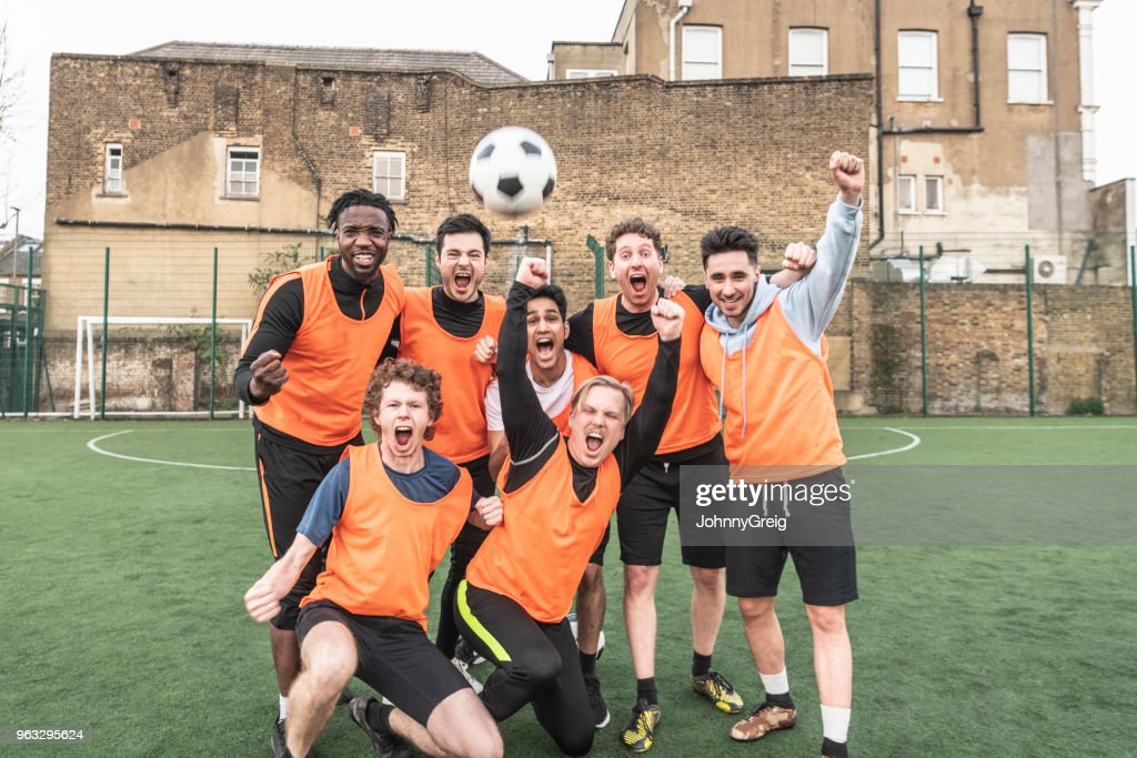 Seven a side football team cheering with ball in the air : Stock Photo