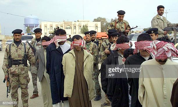Seven alleged insurgents arrive blindfolded under the protection of Iraqi soldiers to the border police station in the holy city of Najaf south of...