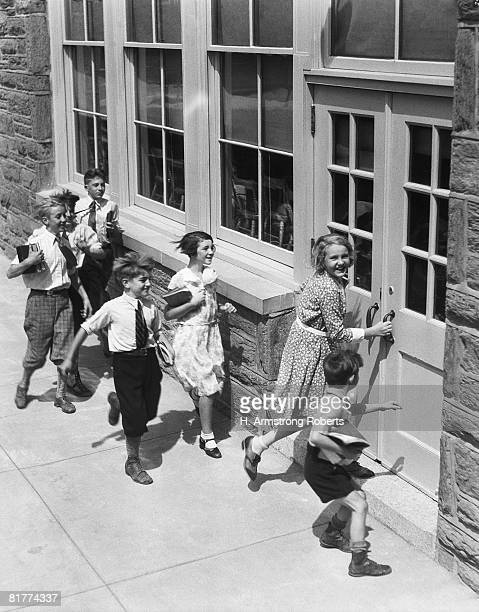 seven children carrying books, about to enter schoolhouse. (photo by h. armstrong roberts/retrofile/getty images) - bambini scuola bianco e nero foto e immagini stock