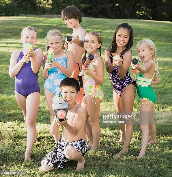 Seven children (7-12) holding squirt guns outdoors, portrait