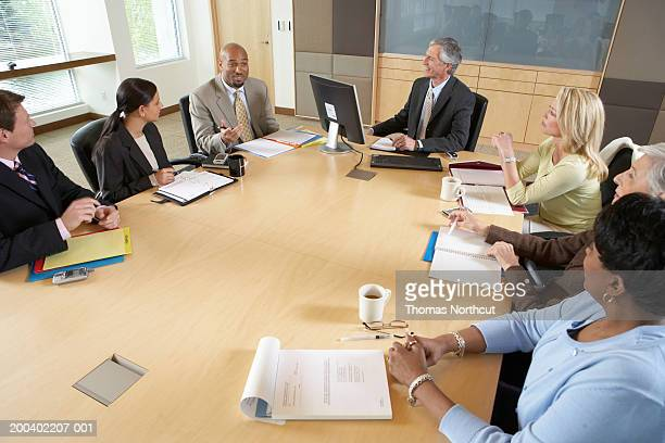 Seven executives meeting in boardroom, elevated view
