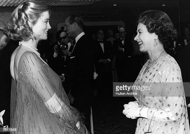 Seven months pregnant American actress Cybil Shepherd meets Queen Elizabeth II at the Royal Film Premiere of 'The Lady Vanishes' in which Shepherd...