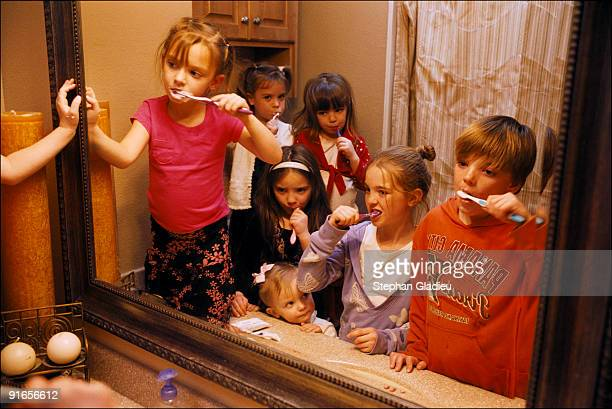 Seven of the 21 children of a polygamist family brush their teeth in one of the five bathrooms of the house they share with their father and three...