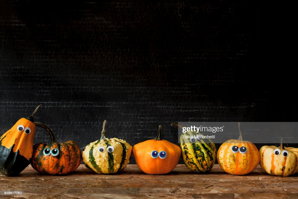 Seven pumpkins with eyes in a row for Halloween : Stock Photo