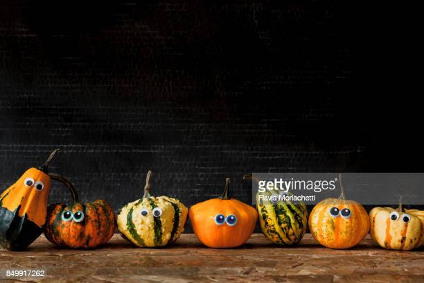 seven pumpkins with eyes in a row for halloween - halloween lantern stock photos and pictures