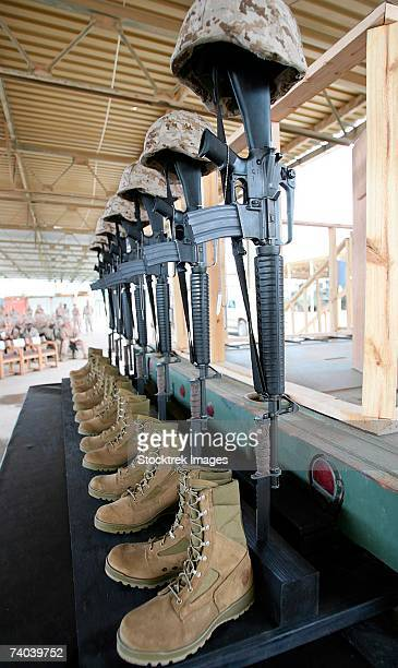 seven sets of dog tags, boots, rifles mounted into the ground with fixed bayonets, and helmets were used to represent six marines and one sailor at a memorial service april 18, 2006, at camp al asad, iraq. - boots rifle helmet stock pictures, royalty-free photos & images
