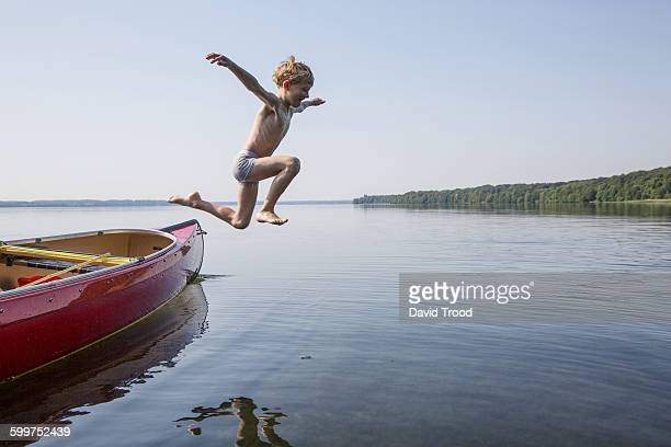 Seven year old boy jumping from a canoe.