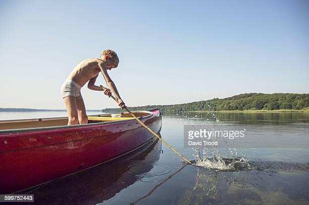 Seven year old boy playing around a canoe.