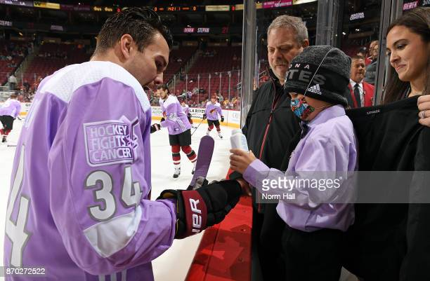 Seven year old Bruce who is battling leukenia adds some powder to the glove of Zac Rinaldo of the Arizona Coyotes before the start of a game against...