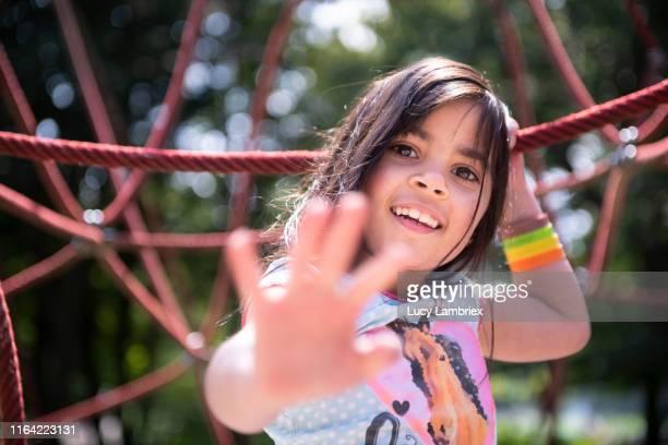 seven year old girl climbing ropes at a playground - activité de plein air photos et images de collection