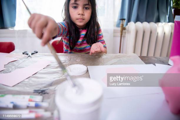 seven year old girl crafting a piggy bank - pink tube photos et images de collection