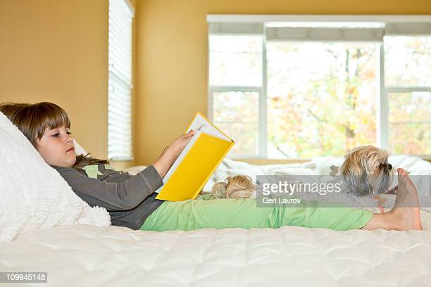 Seven year old girl reading next to her dog