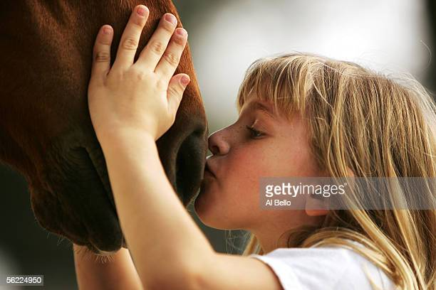 Seven year old Nicole Bello kisses the horse she will be riding prior to he riding lesson at The Thomas School of Horsemanship on April 21, 2005 in...