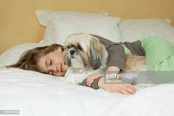 Seven year old sleeping next to her dog (Shih Tzu)