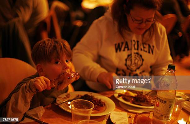 Seven year old Timo Borchardt and his grandmother Carmen Erdmann eat a goose leg at the 13th annual Christmas Celebration for the Homeless at the...