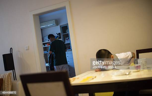 Seven year old Wei Yueran who also has the English name Harney finishes his breakfast while his father Wei Hua checks his schoolbag at home in...