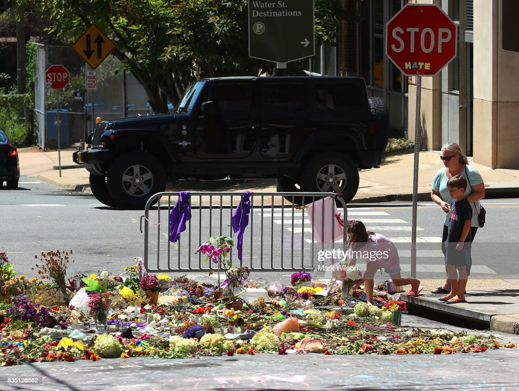 Seven year-old Lily Holtz places flowers on the street where Heather Heyer was killed and 19 others injured when a car slammed into a crowd of people protesting against a white supremacist rally, August 18, 2017 in Charlottesville, Virginia. A participant in a white nationalist, neo-Nazi rally allegedly drove his car into the crowd of people demonstrating against the 'alt-right' gathering.