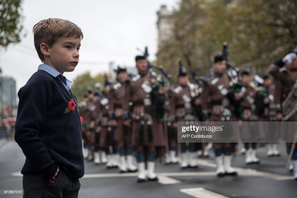 Seven year-old Mylo Jones (L) watches the ceremonies during the Western Front Association's (WFA) annual service of remembrance on Armistice Day, at the Cenotaph in central London on November 11, 2017. /