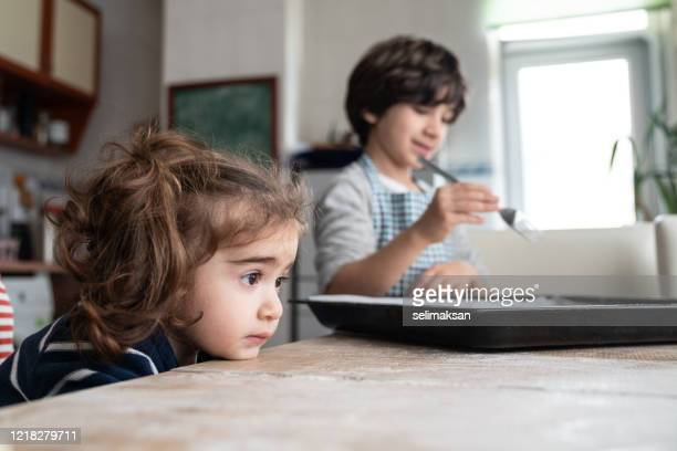 seven years old boy and baby sister cooking - 6 7 years stock pictures, royalty-free photos & images