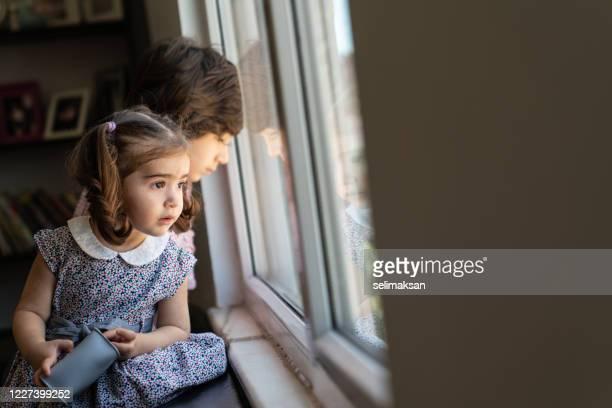 garçon de sept ans regardant par la fenêtre avec sa soeur pendant l'aïd en turquie - eid al adha photos et images de collection