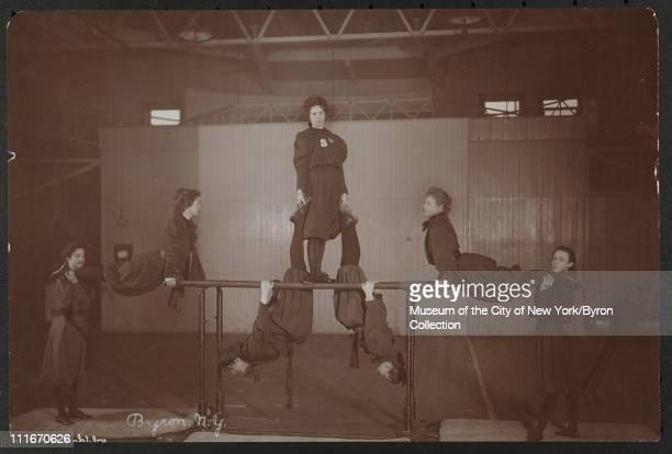 Seven young woman doing gymnastics on the bars New York New York 1899