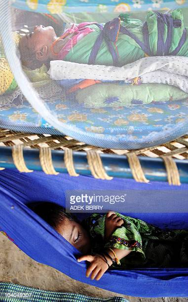 Seven-day-old Suriyat rests under a net on top of a charpoi as her four-year-old sister Zinath takes a nap in a makeshift hammock hanging from the...