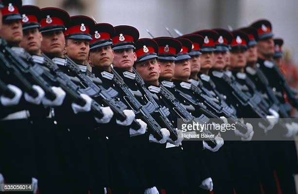Seventeen officer cadets march in line wearing full dress uniform with their rifles on shoulders past guests and VIPs at their passing out parade in...