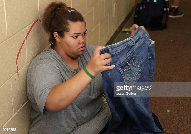 Seventeen yearold Marissa Hamilton inspects a pair of jeans that she borrowed from a friend since her pants no longer fit her at Wellspring Academy...