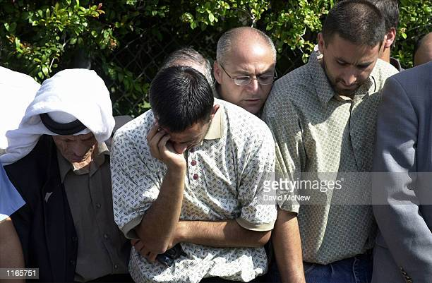 Seventeenyearold Ihsan Nimer watches as the body of his father Abdullah Mohammed Nimer is lower into his grave during funeral services October 10...