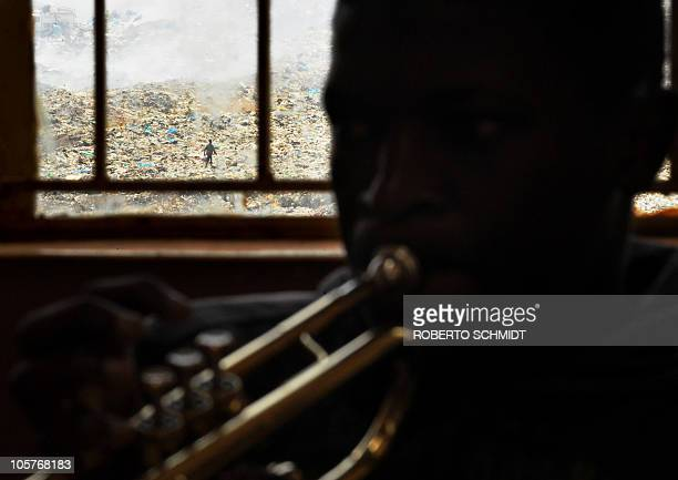 Seventeen-year-old Steve Odieno blows into a trumpet during band practice at a local school in the Korogocho slum in Nairobi on October 16, 2010 as...