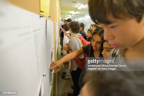 Seventh graders Sasha Nourian, left, and Sidra Hamid, center, search a list for their home room on the first day of school at New West Charter School...