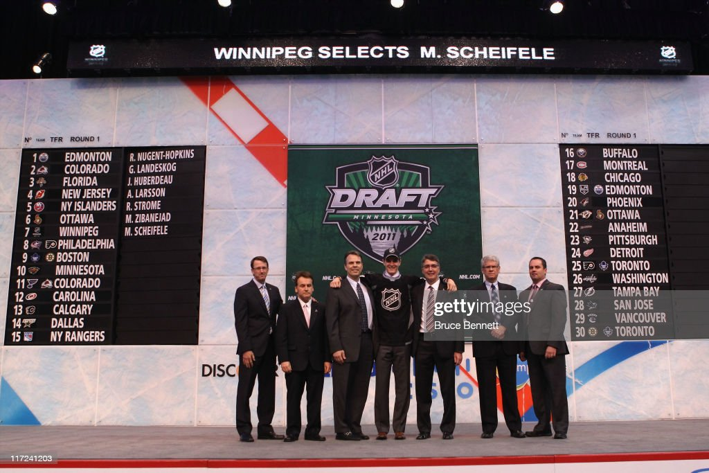 Seventh overall pick Mark Scheifele by the Winnipeg Jets stands at the podium for a photo with members of the Winnipeg Jets organization during day one of the 2011 NHL Entry Draft at Xcel Energy Center on June 24, 2011 in St Paul, Minnesota.