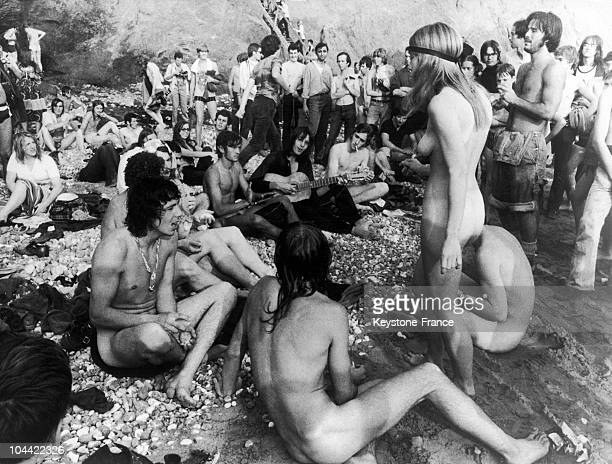 Seventies A Group Of Naked Hippies Singing On The Beach
