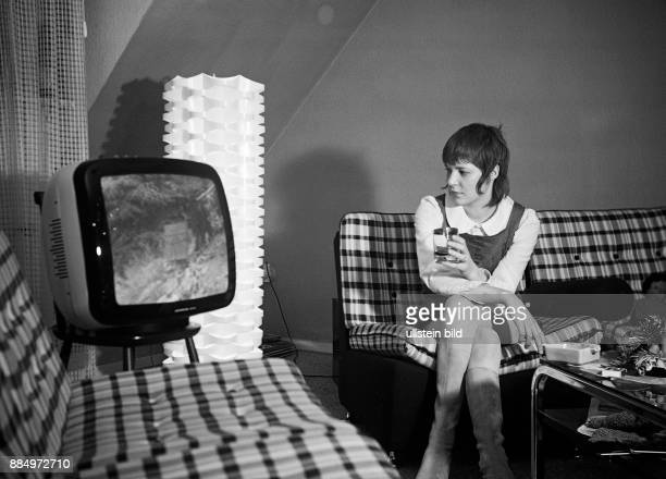 Seventies black and white photo people woman 18 to 22 years on a couch in the living room watching TV shorthaired miniskirt high boots Monika