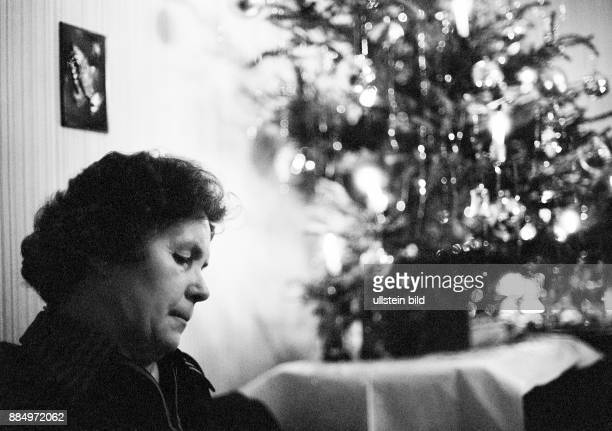 Seventies black and white photo people woman 50 to 65 years lonely sitting in the living room behind the Christmas decoration loneliness sadly...