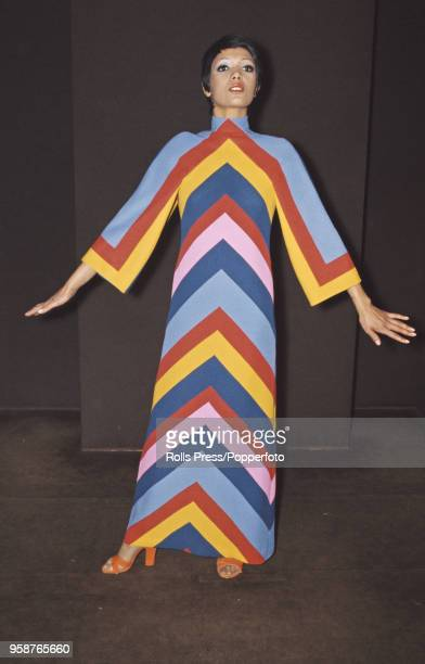 Young female model wears a 'dancing girl' full length evening dress in rainbow coloured chevron stripes, designed by French fashion designer Guy...