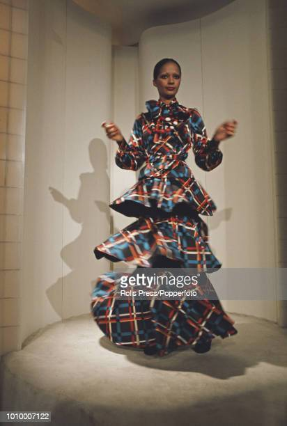 A young female model wears a full length threetiered dress with neck bow in red blue and orange checks by French fashion designer Emanuel Ungaro at...