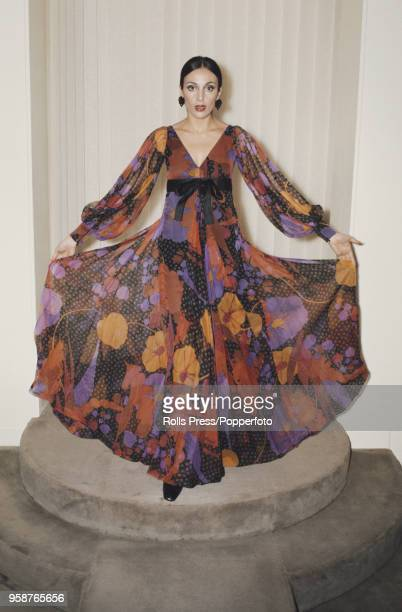 Young female model wears a long empire line maxi dress in silk organdie printed in red, orange, black and violet with pleated layers and puffed...