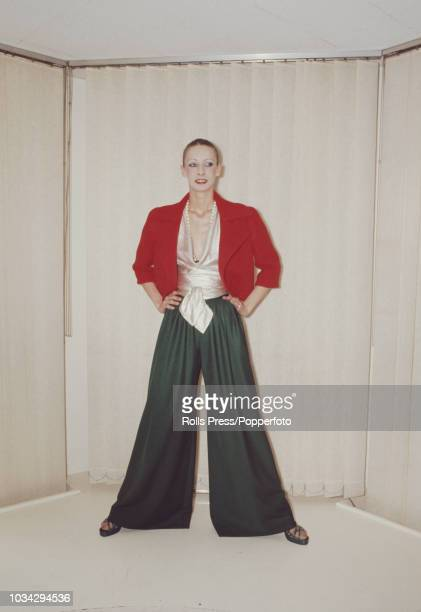 Young female model wears an evening ensemble composed of wide legged green jersey pants, silver plunging neck blouse and a reversible red wool...