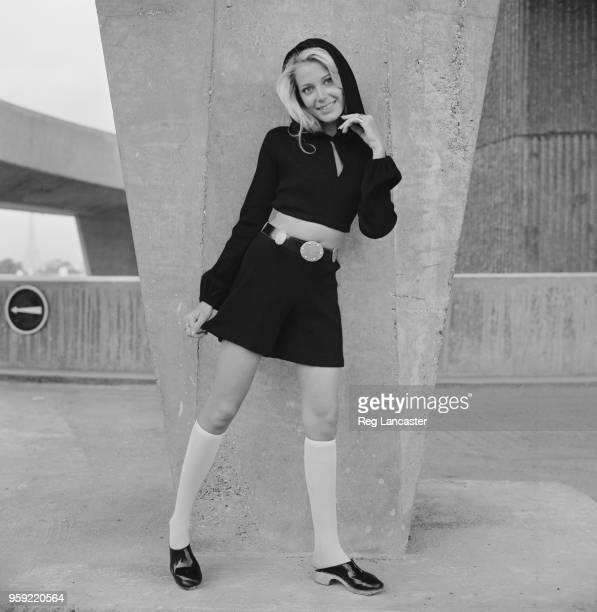 Seventies Fashion - a young female model wears black French shorts and cropped bolero style top with hood, knee length socks and clogs in front of a...