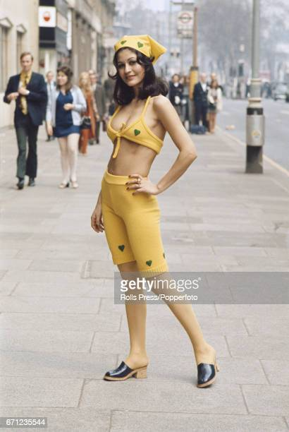 Seventies Fashion Iranian born model Nafiseh wears a pair of yellow knitted long johns with a heart motif along with a matching bikini top and head...