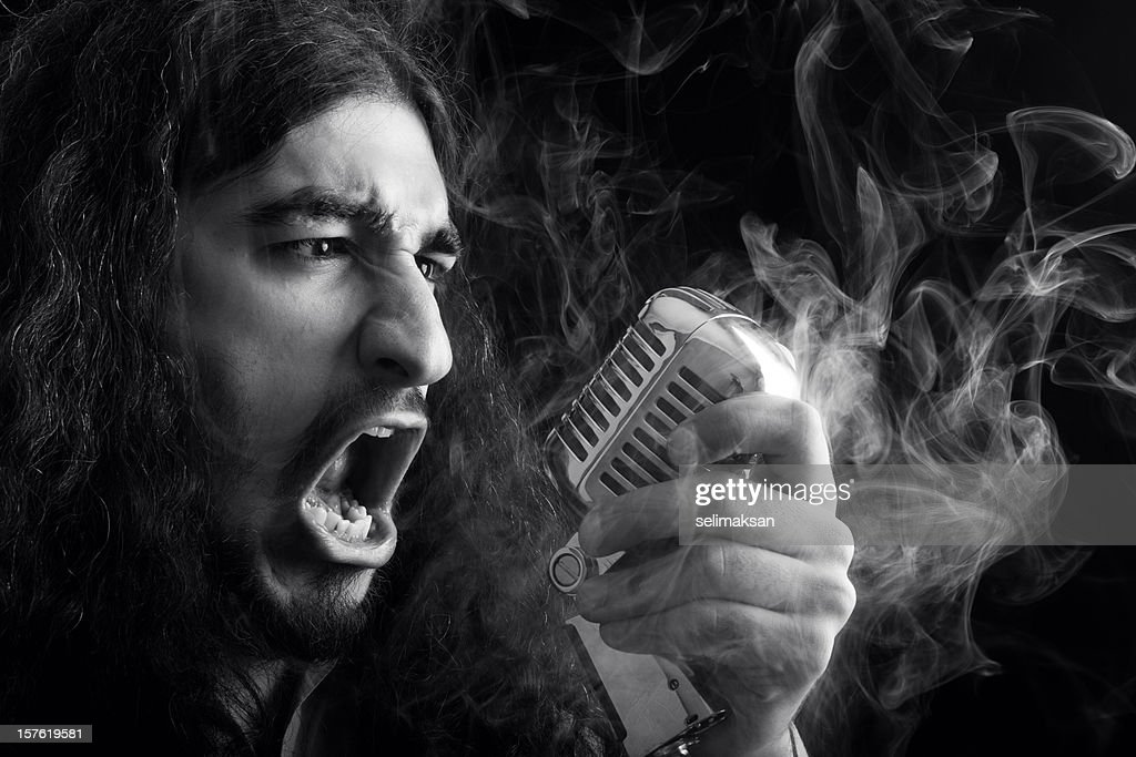 Seventies rock star singing on old fashioned microphone in smoke : Stock Photo