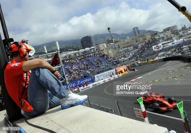 Seventime drivers champion and Ferrari team adviser Mickael Schumacher watches Ferrari's Finnish driver Kimi Raikkonen driving from the pits of the...