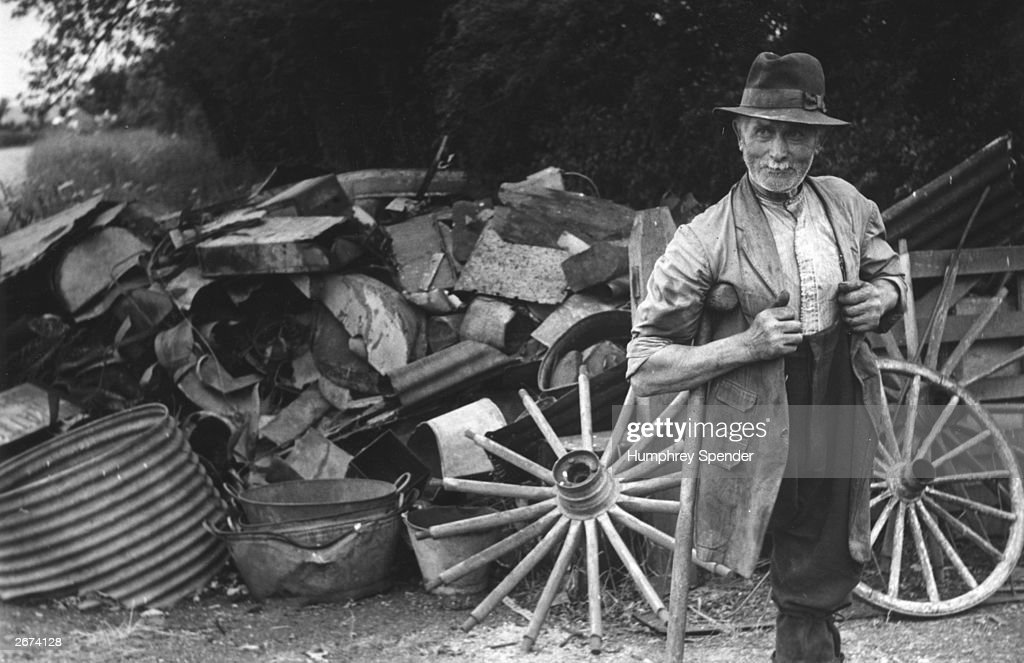 Seventy- two year old scrap dealer Ernest Camden, who lost a leg in an injury, lives in a caravan near Wootton Bassett, surrounded by scrap metal and agricultural refuse. Original Publication: Picture Post - 6008 - High Summer In Ageless Wiltshire - pub. 1952