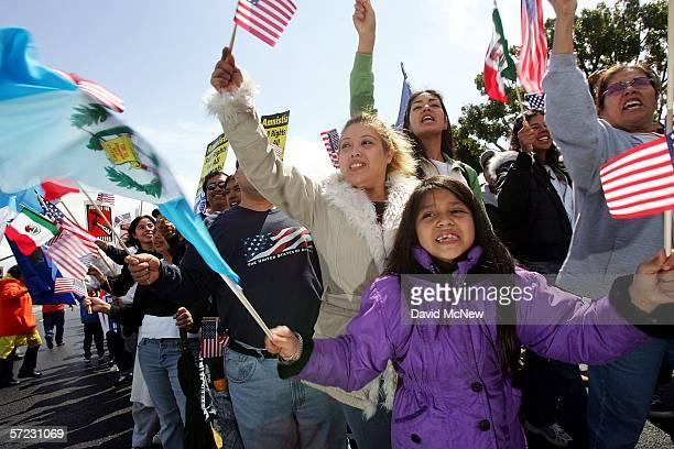 Sevenyearold April Palazios whose parents came from Guatemala waves Guatemalan and US flags as protesters march to decry pending federal legislation...