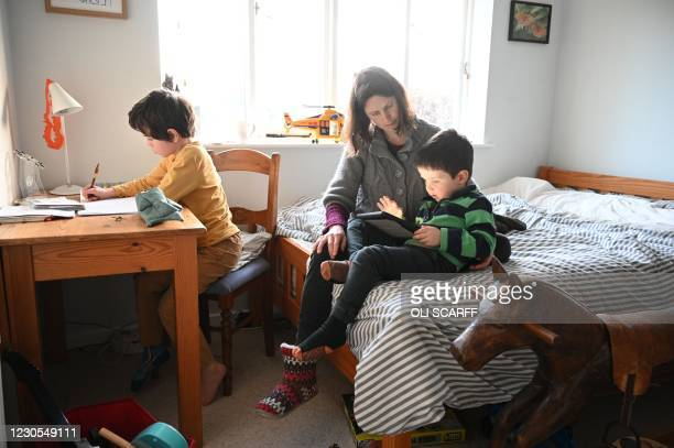 Seven-year-old Leo , and four-year-old Espen are watched by their mother Moira as they complete their remote learning tasks, set by their local...