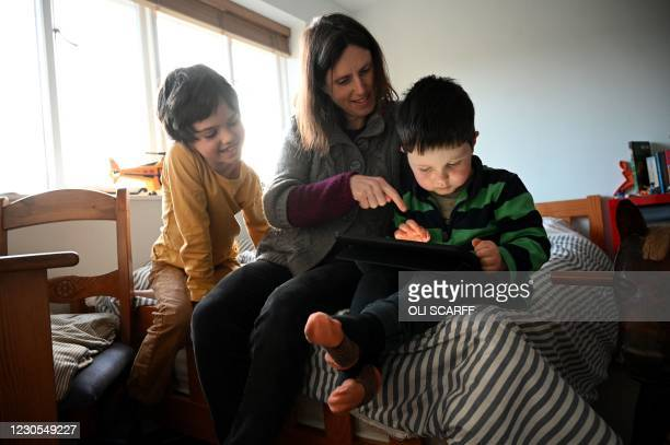 Seven-year-old Leo , watches as his four-year-old brother Espen is helped by their mother Moira to complete their remote learning phonics task, set...